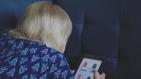 Маленькая девочка используя таблетку сидя на кресле дома ища что-то в онлайн магазине Ходящ по магазинам, социальные средства мас видеоматериал