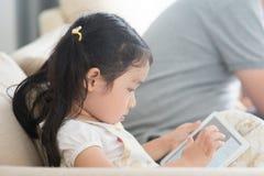 Маленькая девочка используя цифровую таблетку стоковая фотография rf