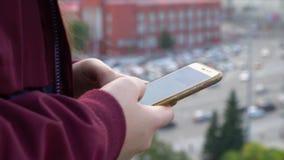 Маленькая девочка используя smartphone сидя на крыше Девушка с длинными волосами на здании крыши в центре города _ акции видеоматериалы
