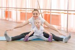 Маленькая девочка и ее мать делают спорт Стоковые Фотографии RF
