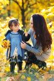 Маленькая девочка и ее мать играя в осени паркуют стоковое изображение rf