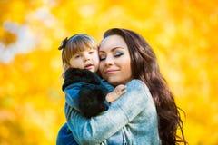 Маленькая девочка и ее мать играя в осени паркуют стоковые фотографии rf