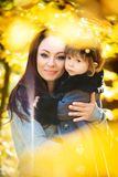 Маленькая девочка и ее мать играя в осени паркуют стоковые изображения rf