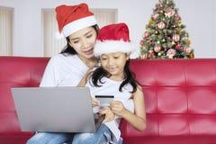 Маленькая девочка и ее мать с кредитной карточкой Стоковые Изображения RF