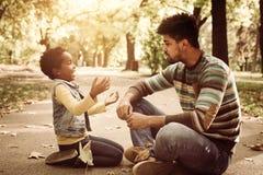 маленькая девочка и ее отец сидя на дороге в парке и стоковое изображение rf