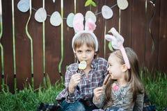 Маленькая девочка и мальчик едят печенье пряника в форме пасхального яйца Стоковое Изображение RF