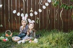 Маленькая девочка и мальчик едят печенье пряника в форме пасхального яйца Стоковое фото RF