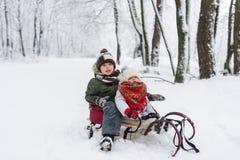 Маленькая девочка и мальчик наслаждаются ездой саней Sledding ребенка Ребенк малыша ехать розвальни Игра детей outdoors в снеге Стоковые Изображения RF