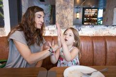 Маленькая девочка и мать в ресторане играя с руками Стоковое Изображение RF