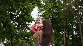 Маленькая девочка и мать одели в элегантных платьях играют в теплом зеленом парке Счастливые мать и младенец отдыхают для прогулк сток-видео