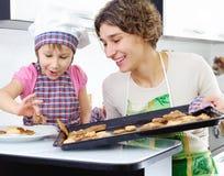 Маленькая девочка и мать с испеченными печеньями стоковые изображения