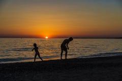 Маленькая девочка и подросток играя на пляже на заходе солнца стоковые изображения