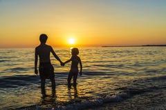 Маленькая девочка и подросток купая на пляже на заходе солнца Стоковое Фото