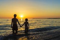 Маленькая девочка и подросток купая на пляже на заходе солнца Стоковая Фотография