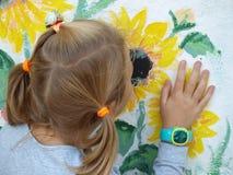 Маленькая девочка касается ее руке и обнюхивается желтые солнцецветы покрашенные на белой стене стоковая фотография rf