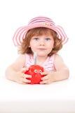 Маленькая девочка кладя примечание евро в ее piggy банк Стоковое фото RF