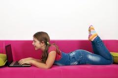 Маленькая девочка лежа в кровати и играя компьтер-книжку Стоковая Фотография