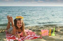 Маленькая девочка лежа на сезоне лета пляжа стоковое изображение rf
