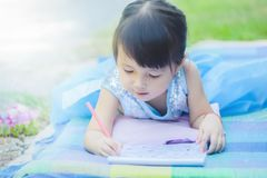 Маленькая девочка лежа с книгой чертежа на циновке в парке с счастливой стороной когда ее релаксант в празднике утра стоковая фотография