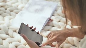 Маленькая девочка лежит на белой шотландке в парке и набирает сообщение на телефоне сток-видео