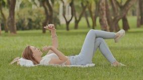 Маленькая девочка лежит на ей назад в зеленой траве с smartphone в ее руках Потеха представляя на телефоне камеры воссоздание видеоматериал