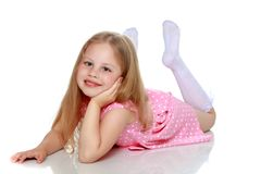 Маленькая девочка лежит на поле стоковое изображение