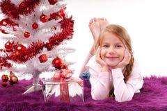 Маленькая девочка лежит с подарком рождества Стоковые Фотографии RF