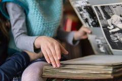 Маленькая девочка листая через альбом семьи стоковое фото rf