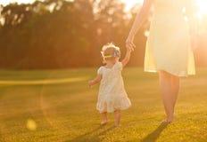 Маленькая девочка мамы идет слепимости лучей захода солнца руки травы Стоковое Изображение RF
