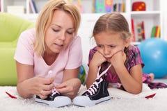 Маленькая девочка матери учя для того чтобы связать ее ботинки стоковые изображения rf
