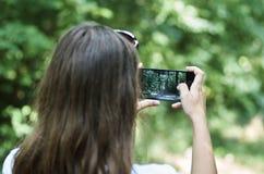 Маленькая девочка мобильным телефоном фотографирует ландшафт с a стоковое фото