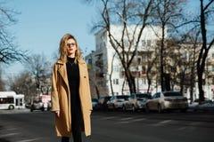 Маленькая девочка моды в стеклах Белокурые, красные губы, бежевое пальто идя вдоль улицы города стоковое фото rf