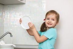 Маленькая девочка моет блюда стоковое фото rf