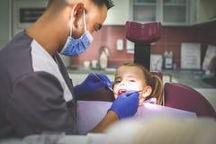Маленькая девочка молодого мужского дантиста рассматривая Стоковая Фотография