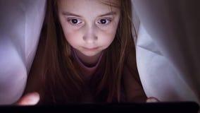 Маленькая девочка наблюдает видео покрытое с одеялом акции видеоматериалы