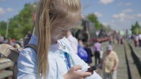Маленькая девочка наблюдая ее умный телефон в вокзале пока ждет сток-видео