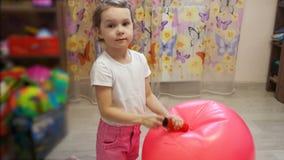 Маленькая девочка нагнетает шарик в комнате акции видеоматериалы