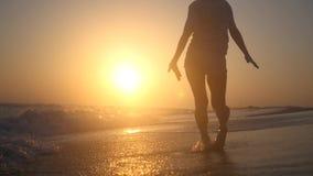 Маленькая девочка наслаждается заходом солнца и морем, скача на воду с счастьем HD, 1920x1080 движение медленное акции видеоматериалы