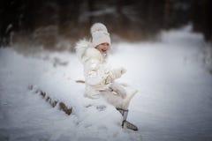Маленькая девочка наслаждаясь днем вне играя в лесе зимы Стоковое Изображение