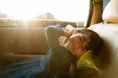 Маленькая девочка наслаждаясь отключением в заднем сидении стоковые фото