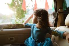Маленькая девочка наслаждаясь отключением в заднем сидении стоковое фото rf