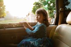 Маленькая девочка наслаждаясь отключением в заднем сидении стоковая фотография rf