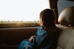Маленькая девочка наслаждаясь отключением в заднем сидении стоковые фотографии rf