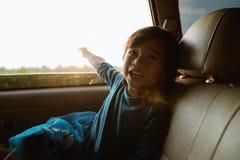 Маленькая девочка наслаждаясь отключением в заднем сидении стоковые изображения