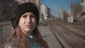 Маленькая девочка на железнодорожном вокзале Оягнитесь ждать поезд и счастливый о путешествии Люди, перемещение, семья, образ жиз сток-видео