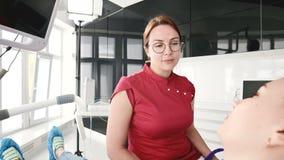 Маленькая девочка на консультации с женщиной дантиста в стеклах сидит на стуле в офисе stamotology _ акции видеоматериалы
