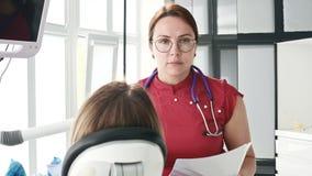 Маленькая девочка на консультации с женщиной дантиста в стеклах сидит на стуле в офисе stamotology _ видеоматериал