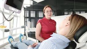 Маленькая девочка на консультации с женщиной дантиста в стеклах сидит на стуле в офисе stamotology _ сток-видео