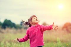 Маленькая девочка на луге в солнечном дне стоковые фото