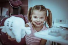 Маленькая девочка на офисе дантиста представляет с игрушкой зубов стоковое изображение rf